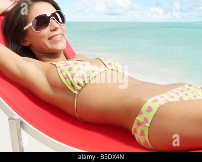 Young Woman Sunbathing on Lounge Chair - Stock Photo