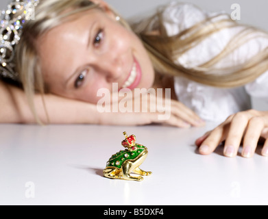Woman Looking at Decorative Frog Prince - Stock Photo