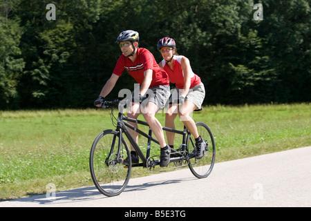 Germany, Bavaria, Oberland, Couple mountain biking on tandem - Stock Photo