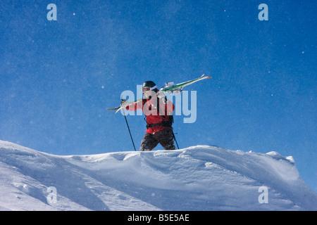 Austria, Tyrol, Zillertal, Gerlos, Freeride, Man carrying skis over shoulders - Stock Photo