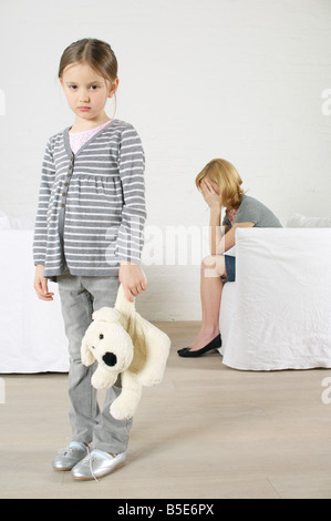 Despaired woman sitting in armchair, girl holding stuffed animal standing in foreground - Stock Photo