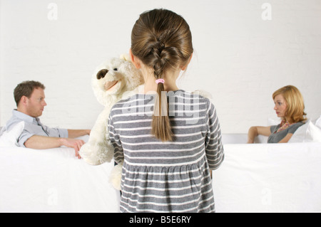 Frustrated couple sitting vis-à-vis, girl holding teddy bear standing in foreground - Stock Photo