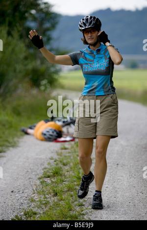 Germany, Bavaria, Oberland, Woman gesturing, fallen biker in background - Stock Photo