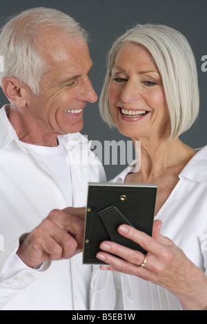 Senior couple looking at a picture - Stock Photo