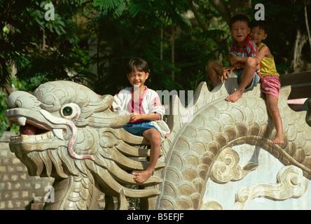 Children sitting on dragon Long Son Pagoda Nha Trang Vietnam Indochina Southeast Asia Asia - Stock Photo