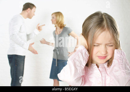 Couple arguing, girl in foreground covering ears with hands - Stock Photo