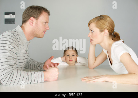 Couple arguing at table, girl in background covering ears with hands - Stock Photo
