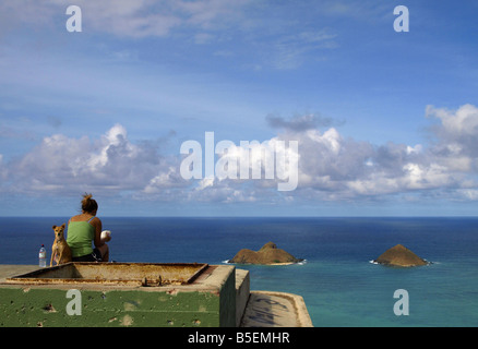 Woman sitting on an abandoned military bunker at Lanikai ridge - Stock Photo