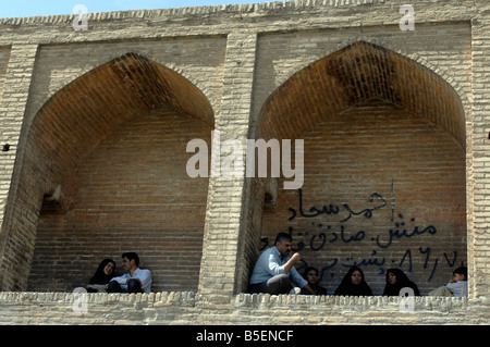 Iranians gather in the arches of the 298m Si-o-Seh Bridge, Esfahan - Stock Photo