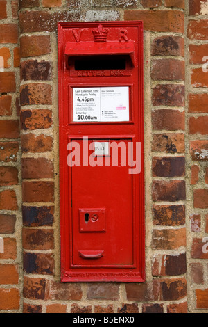 red post box in a wall in UK - Stock Photo
