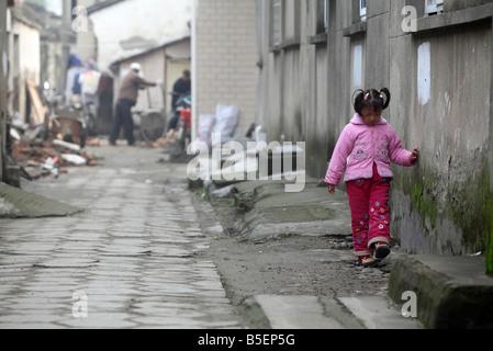 A young bored Asian girl walking along a wall, Suzhou, China - Stock Photo