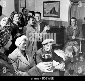 Hop pickers with local men drinking at a country pub in Kent after a hard day's workCirca 1930 - Stock Photo