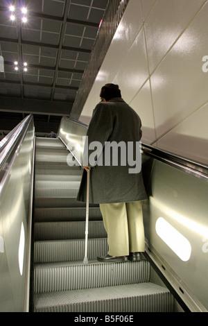 Old man on an escalator, Berlin, Germany - Stock Photo