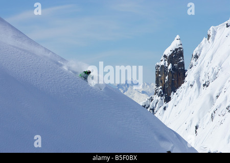 Skier doing a tight turn on intact snow - Stock Photo