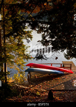 Red and Blue kayak on a dock in Canadian cottage country with fall colours - Stock Photo