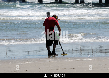 Man using metal detector on beach - Stock Photo