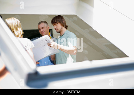 Young couple and architect conferring at construction site - Stock Photo
