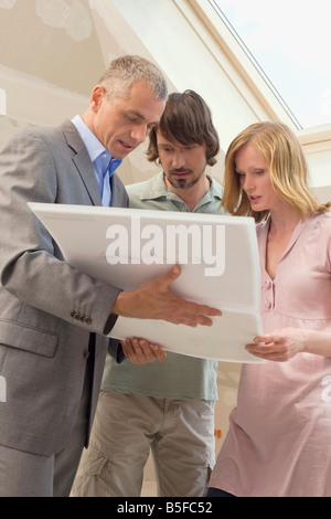 Architect discussing construction plan with young couple - Stock Photo