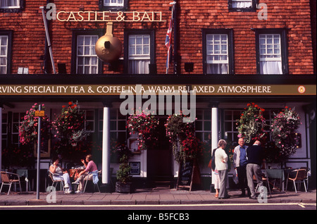 People standing and sitting before the Castle & Ball inn on High Street, Marlborough, Wiltshire, England - Stock Photo