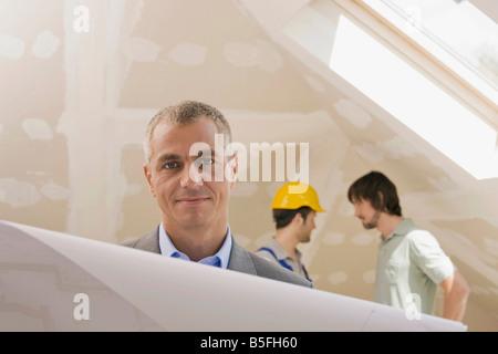 Man holding construction plan, close up - Stock Photo