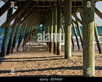 Massive wooden posts support the pier at Myrtle Beach State Park in South Carolina. - Stock Photo
