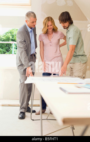 Young couple and architect at site - Stock Photo