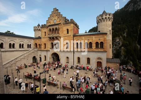 visitors at the courtyard of Neuschwanstein Castle in Schwangau near Fuessen Allgaeu Bavaria Germany - Stock Photo