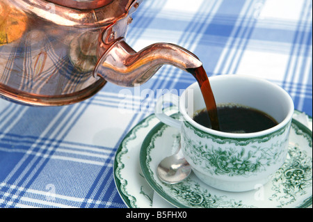 pour out filling up a cup with fresh hot black coffee from an old swedish coffe pot made out of copper - Stock Photo
