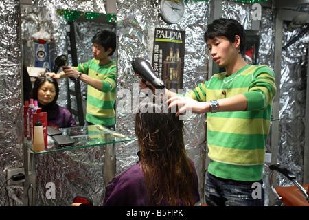 A hairdresser drying hair, Shanghai, China - Stock Photo