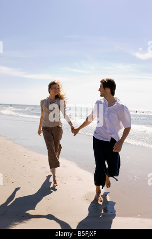 Germany, Baltic sea, Young couple walking across beach, holding hands - Stock Photo