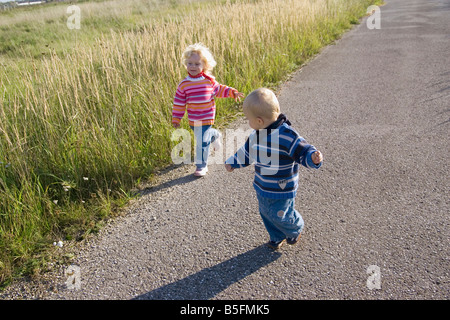 Little girl (2-3) and boy (1-2) running across path - Stock Photo
