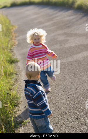 Little girl (2-3) and boy (1-2) playing on path - Stock Photo