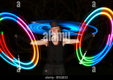 male and female performance artists juggling LED lightstick playing with lights - Stock Photo