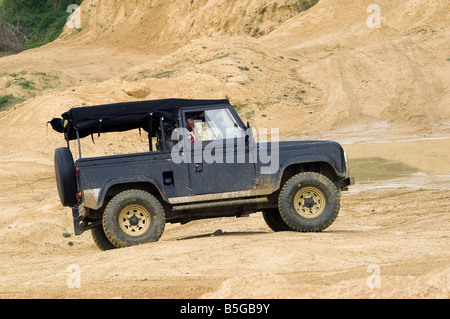 Land Rover defender driving off road in the UK - Stock Photo