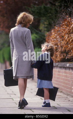 back view of a working mother walking her daughter to school at the start of a new term - Stock Photo