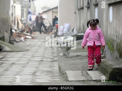 A young bored Asian girl going along a wall, Suzhou, China - Stock Photo