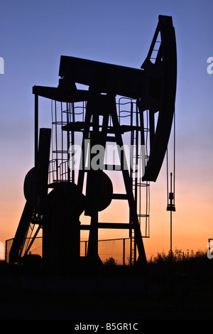 industrial pump jack in the sunset silhouette - Stock Photo