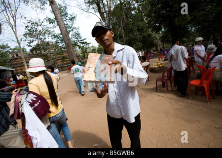 Children selling postcards guidebooks at Angkor Wat temples, Sien Reap, Cambodia - Stock Photo