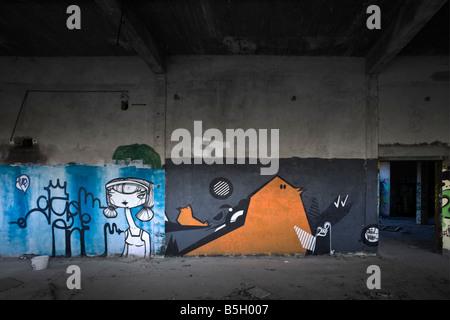 Graffiti in a brownfield site factory. Graffiti dans une usine désaffectée. - Stock Photo