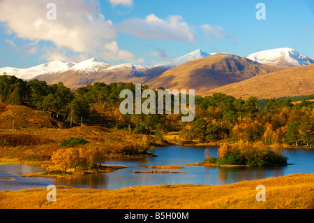 Looking over Loch Dochard near Rannoch Moor scotland with snow covered mountains in the distance