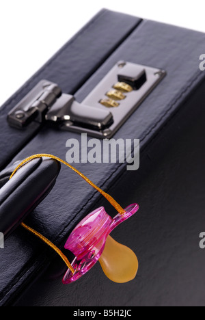 briefcase and a pink soother - Stock Photo