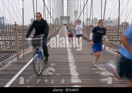 New York NY 3 November 2008 Joggers and cyclists on the pedestrian path of the Brooklyn Bridge - Stock Photo