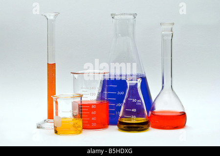 Flasks cylinders and beakers with colorful liquids as pH indicators on a white background - Stock Photo