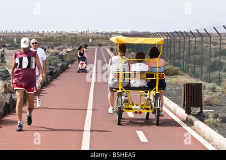 dh  PLAYA DE GUACIMETA LANZAROTE Family riding four wheel buggy on cyclepath people walking cycling path - Stock Photo