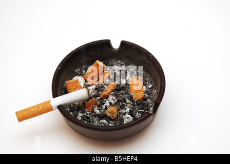 cigarette in a dirty ashtray - Stock Photo