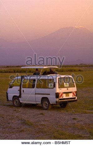 Tourists in a safari vehicle watching the sunset on Mount Kilimanjaro from Amboseli National Park Kenya - Stock Photo