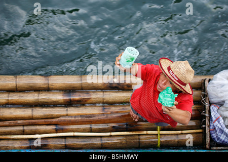 Vendor with jade buddhas on a bamboo raft on the Li River in Guangxi - Stock Photo