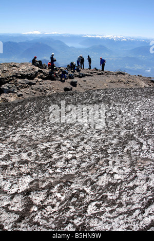 Amateur climbers take a break on the top of active Villarrica Volcano near Pucón, Chile on a sunny summer day. - Stock Photo