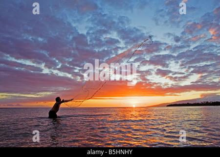A Hawaiian man throws his net at sunset at Olowalu, Maui, Hawaii. - Stock Photo