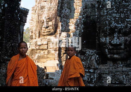 Two young novice monks stand in front of enormous faces carved in stone at Bayon, Angkor Thom, Angkor temple complex, - Stock Photo